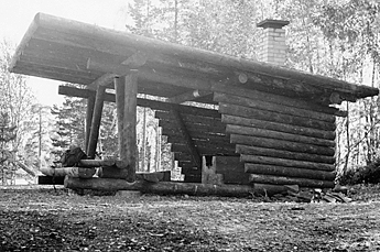 Black and white photo of a cooking shelter in the forest.