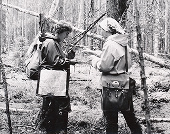 Black and white photo of two women in a forest.