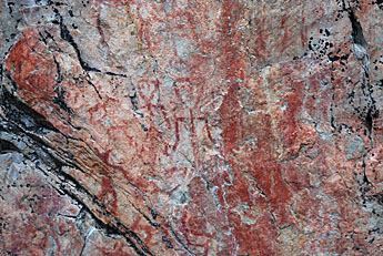 Ancient cliff paintings on the vertical cliff wall.
