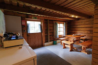 The interior of the hut. The room has log walls and a table and benches.