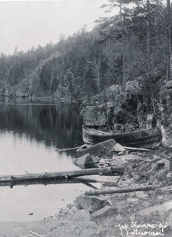 An old black and white photo of a rocky lake beach, with a rowing boat drawn up on it.