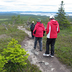 Three hikers walking along a stony path away from the photographer. A lake- and coniferous landscape opens up in the background.