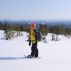 A child on snowshoes standing on a fell slope looking at the photographer.