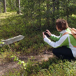A squatting hiker photographing a wooden sign in the forest.