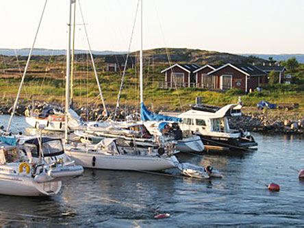 Boats at the dock. A treeless archipelago and three small wooden cabins can be seen in the foreground.