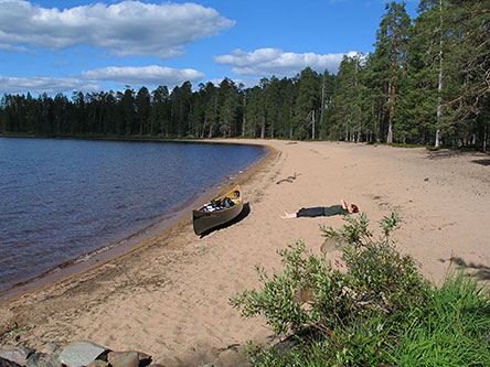 A canoeist resting near their canoe on beach bordered by a forest.