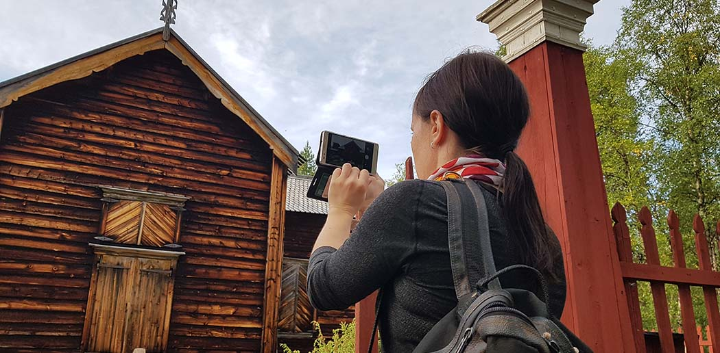A hiker is taking pictures with his mobile phone of an old wooden church. The paint is peeling of the church walls. A dull and cloudy sky in the background.