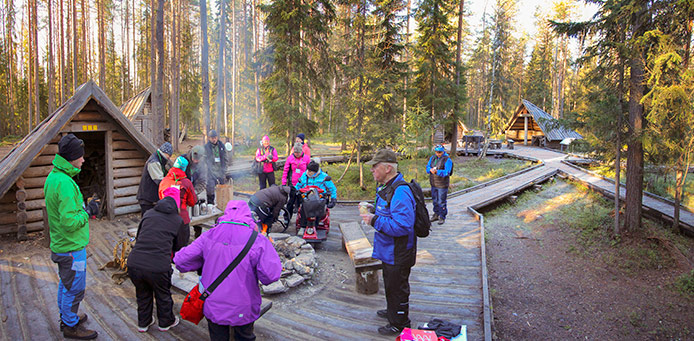 Hikers gathered around a campfire in a plank trail rest area.