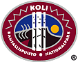 The drawn emblem of Koli national park. Inside the oval symbol are three brirch trees with fells in the background depicted. Smoke is rising from a slash-and-burn site on the fell slope. The text Koli national park wraps around the outer edge of the emblem.