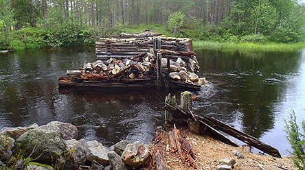 Old flotation structures built of wood and stone have been left in the river. On the shore opposite, you can see forest.