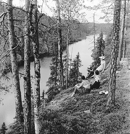 An old, black and white photo of three women sunbathing in summer clothes. The women are sitting in a forest at the top of a high cliff and are looking down at the lake.