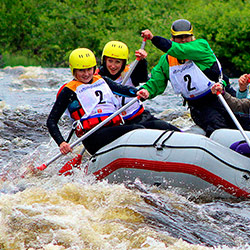 Rafters ride in inflatable boat down the rapids.