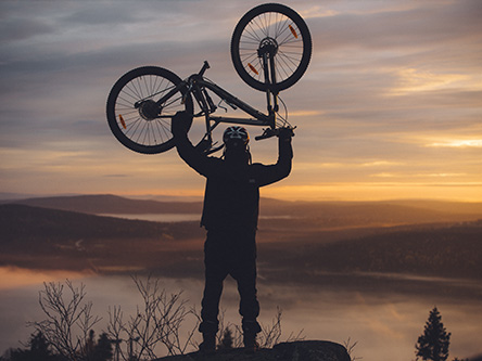 A mountain biker has raised their bike above their head while watching the sunset.
