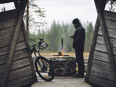A mountain biker has stopped by a fireplace on the Syötteen kierros circle trail.