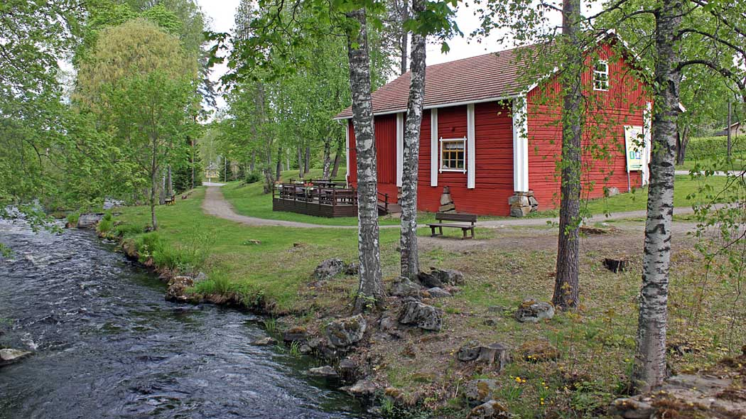 A red nature cottage in a summer landscape. A river flows in the foreground.