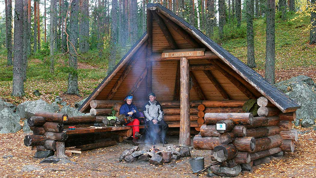 Two hikers by the fire in a campfire shelter. In the background an autumn forest.