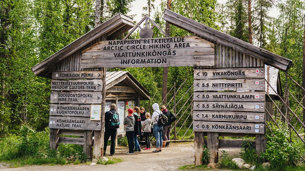 People reading an information board by the gate of the Arctic Circle Hiking Area.