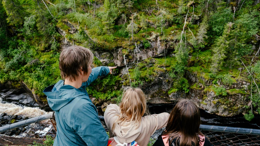 An adult and two kids are leaning on the railing. Adult points to the moss-covered cliffs. River flows below.