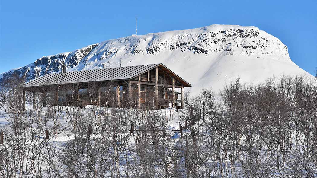 Kilpisjärvi visitor centre seen from outside in winter, with the Saana fell in the background.