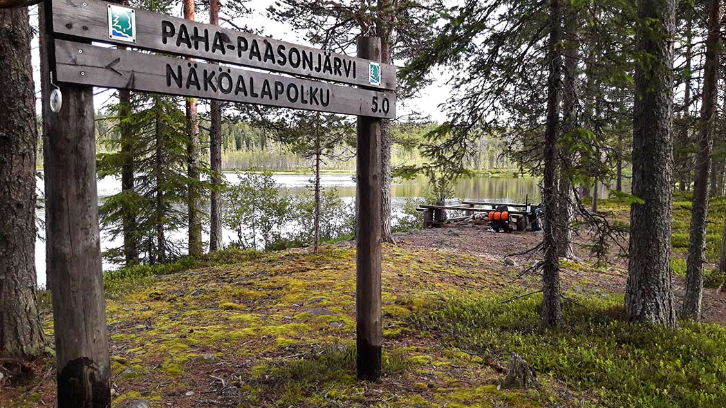 A cooking area surrounded by benches at a lake shore on a dry heath. In the front is a wooden sign with text Paha-Paasonjärvi and another sign showing the way towards a viewpoint trail.