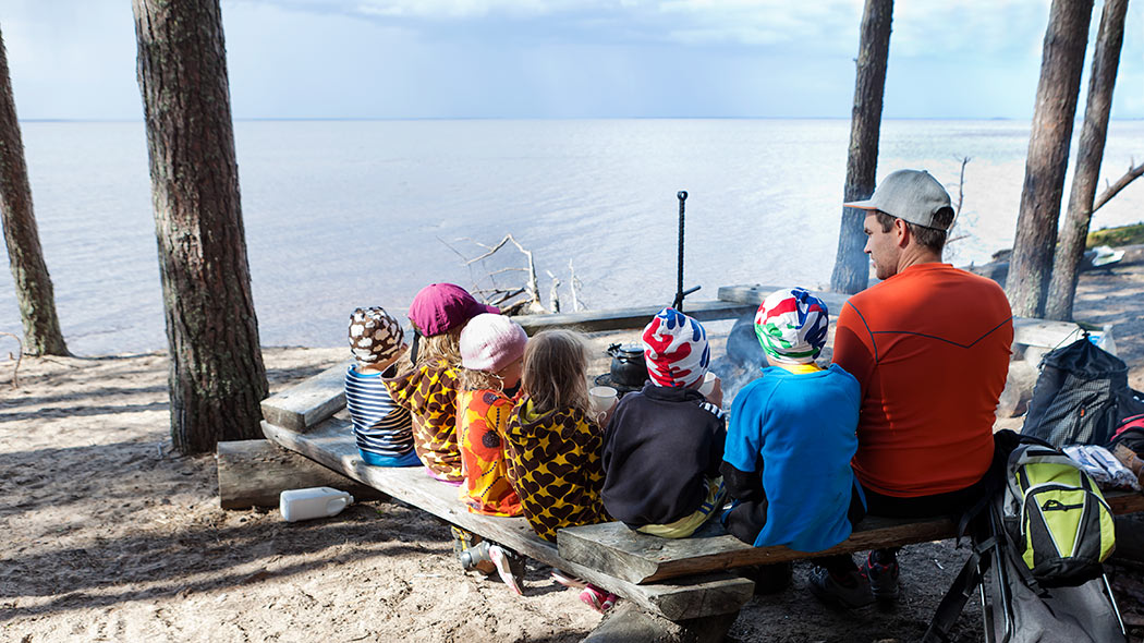A family with children by a campfire. A view of the Oulunjärvi-lake is opening up in the background.