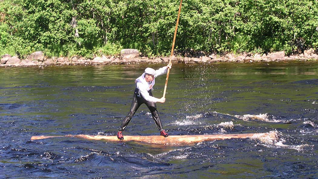 A person running a rapid on a log. The person is balancing on the log, holding a long wooden pole in his hand.