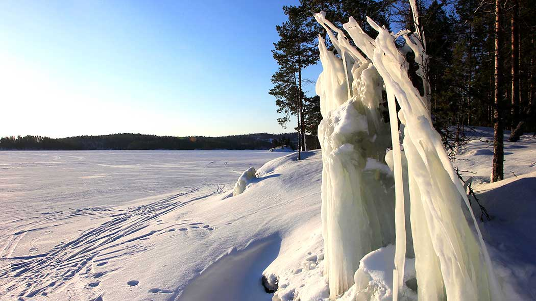 Winter by lake, an ice statue on the beach.