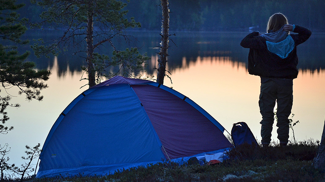 A tent has been set up next to a lake shore. A hiker is standing, and looking out over the calm late. It is evening.