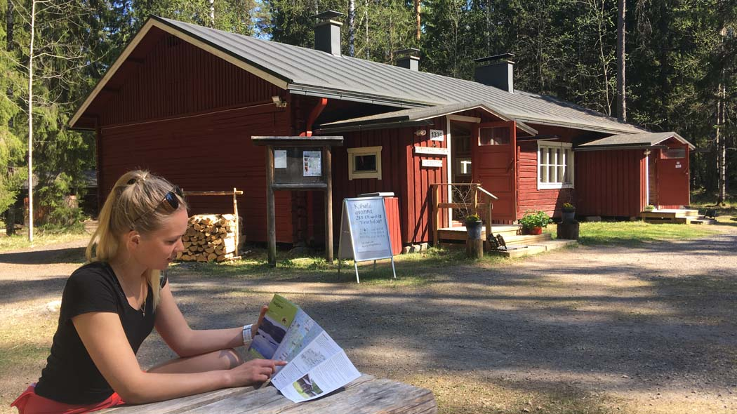 A woman studying a map in front of the Heretty loggers' cabin.
