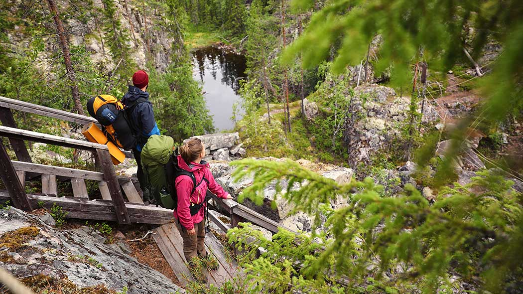 Two hikers with their backbags are standing on the stairs on the edge of the gorge and watching the view down to a small lake. Coniferous forest surrounds the gorge.