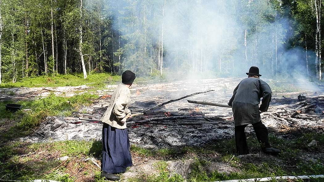 A man and a woman in traditional dress are burning birch in the sunshine.