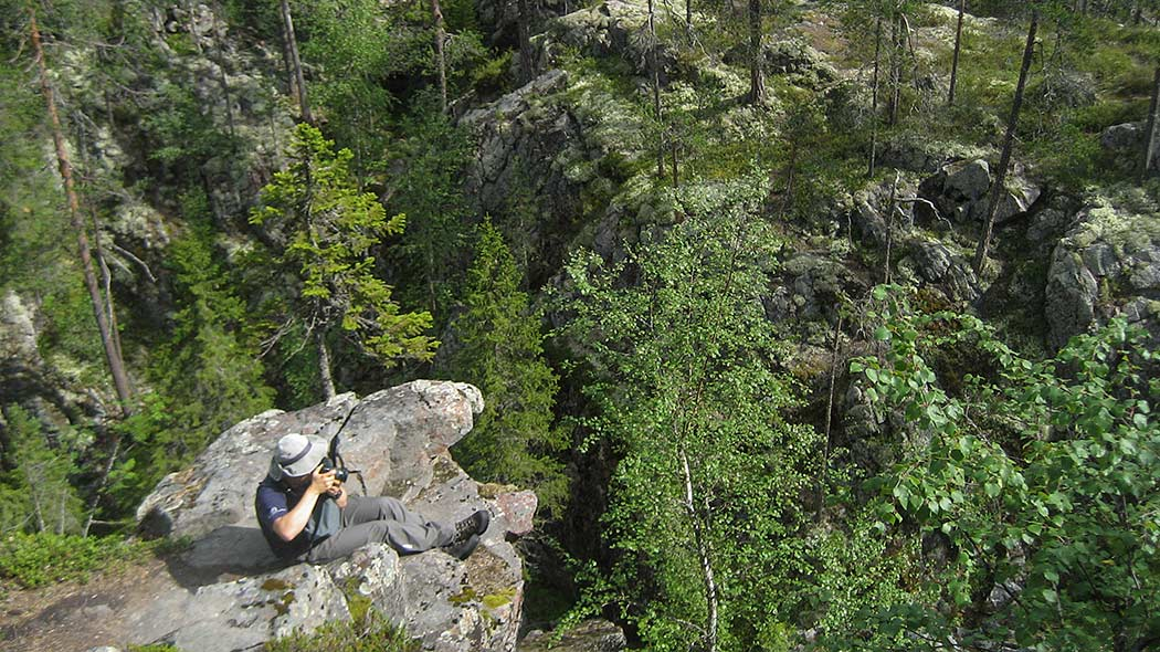 A hiker is sitting on a cliff during the summer and photographing. Green forest and rocky terrain consitutes the background.
