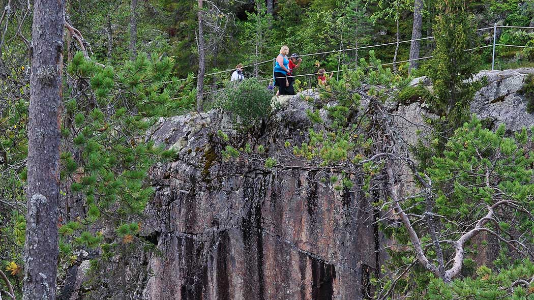 Hikers have climbed up a steep stone wall. There are railings at the top of the wall. Pines spatter the landscape.