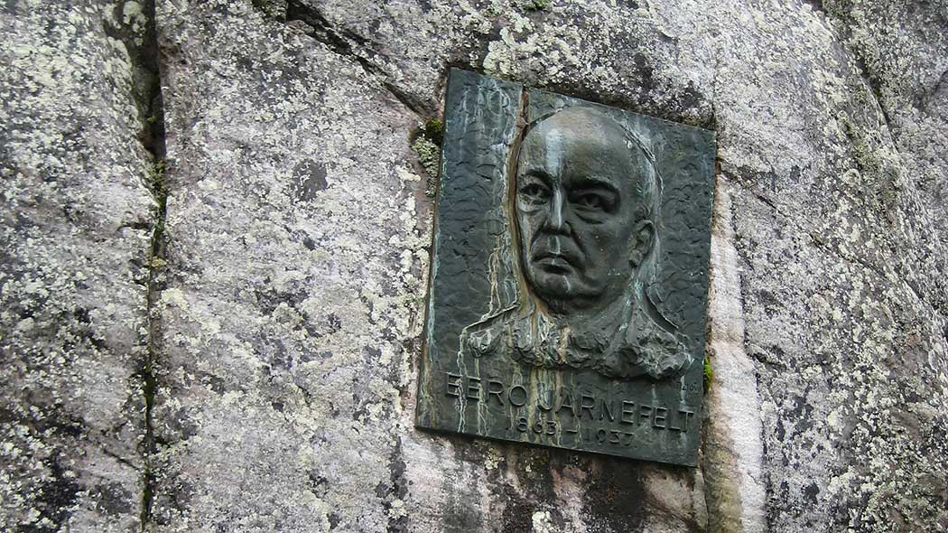 A memorial plaque to Eero Järnefelt is attached to a rock wall. The plate has Järnefelts face, name and the years 1863-1937 engraved.