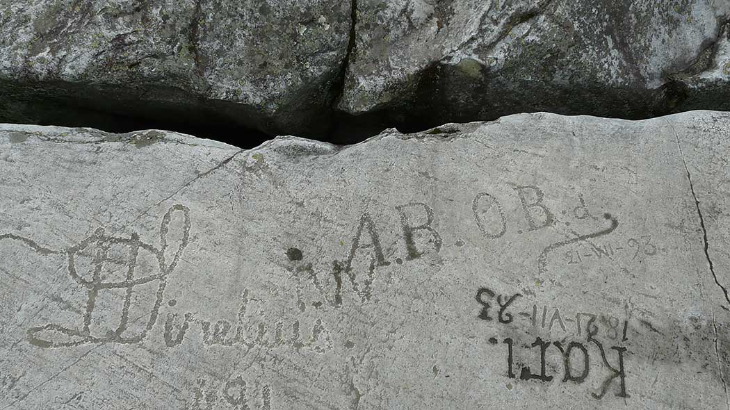Names and nicknames have been engraved in different styles into a rock wall.