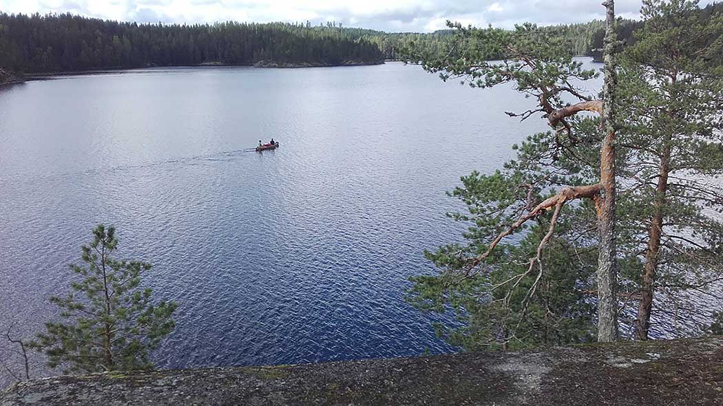 Two paddlers in a summery lake landscape. In the foreground there is forest and a rocky beach.