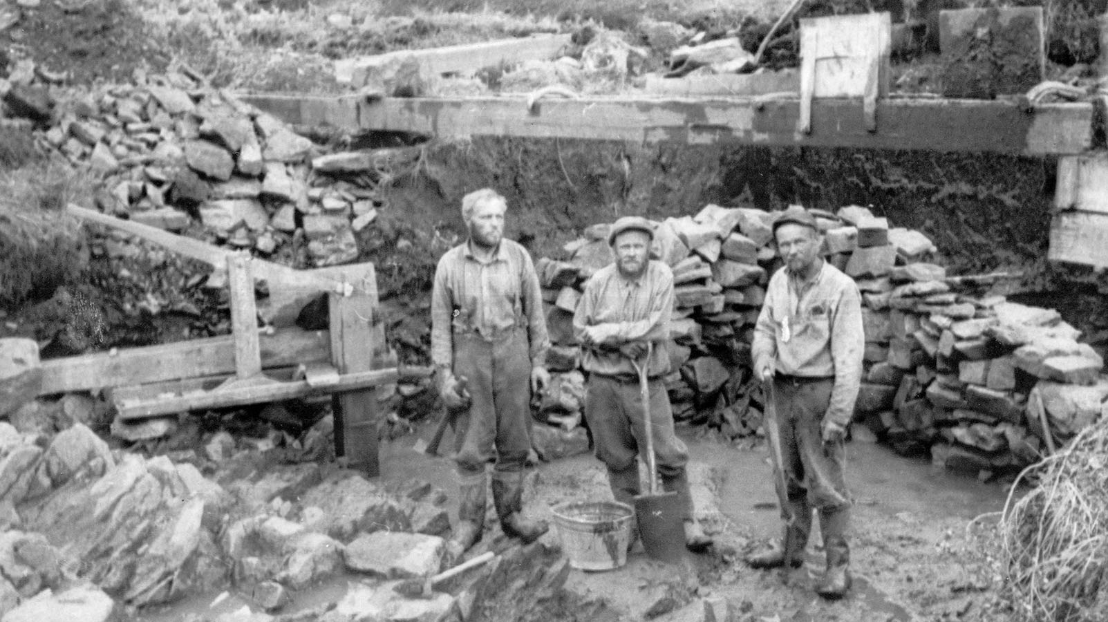 Tree med standing between rocks, two of the men have shovels and the third have a pick in his hand. Behind the men is a tall wooden trough.