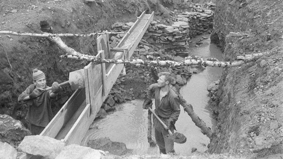 Two men working with shovels in a riverbed. The riverbanks are steep and rocky. There is a long wooden trough running in the direction of the riverbed. A man just emptied his shovel in the trough.