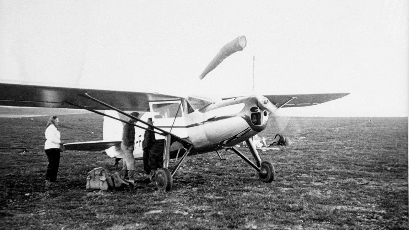 A small airplane waiting in an open area. Two men and a woman standing next to the airplane, a backpack is lying on the ground. A windsock shows the wind direction.