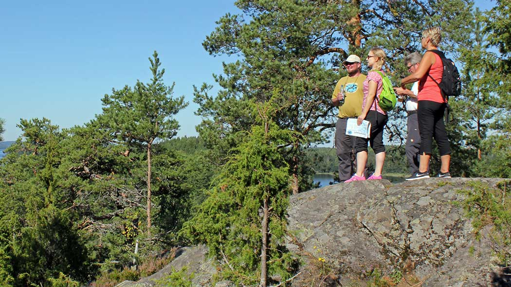 Four hikers standing on a tall rock admiring the beautiful landscape over the archipelago.