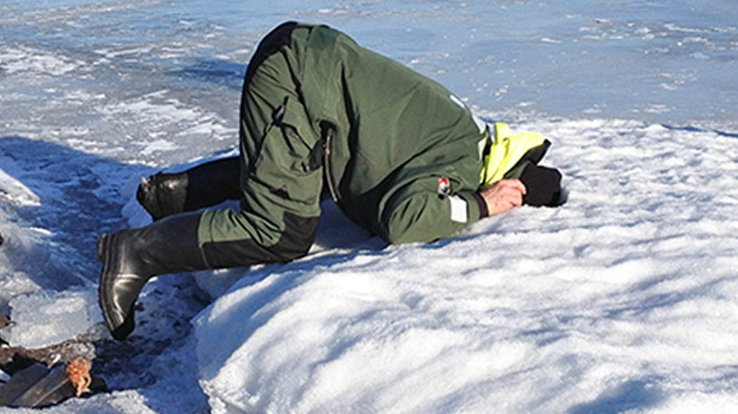 A person is on his bended knees on a frozen lake with his head tucked in the hole that`s in the ice.