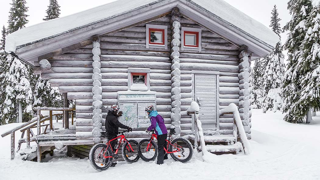 Two mountain bikers are studying a map by the Ahmatupa wilderness hut in winter. The trees and the roof of the hut are covered by a thick layer of snow.
