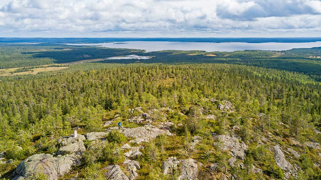 A rocky forest landscape seen from above. There is a lake in the background.