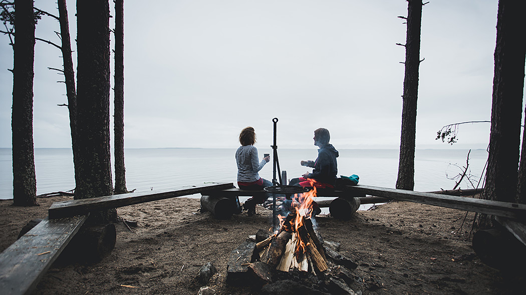 Two hikers at the fireplace by the shore at Oulujärvi hiking area. A misty lake landscape can be seen in the background.