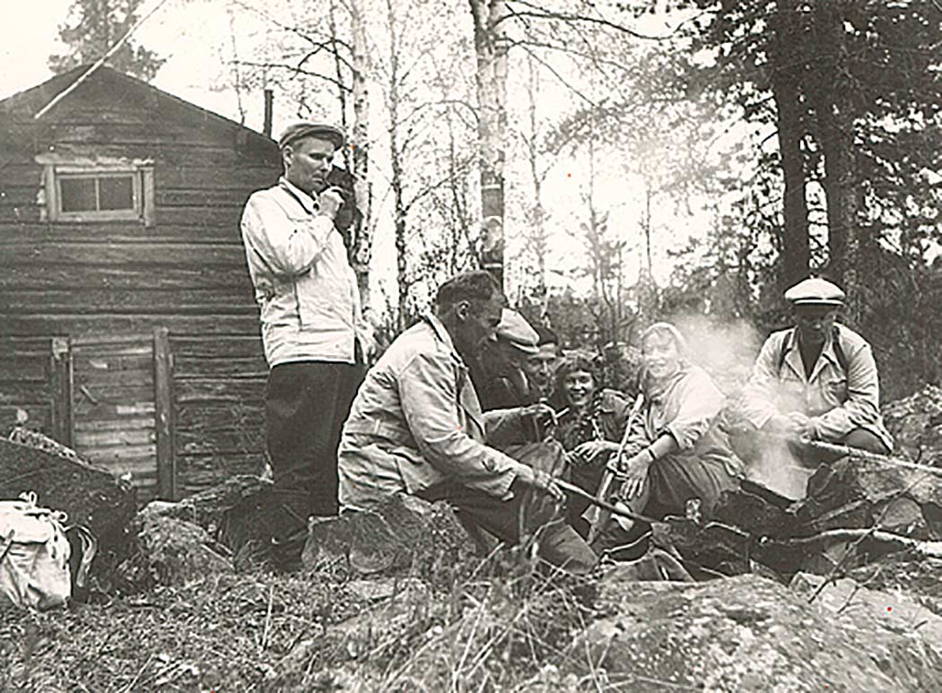 An old black and white photograph where people gathered around a campfire can be seen. There is a log cabin in the background.