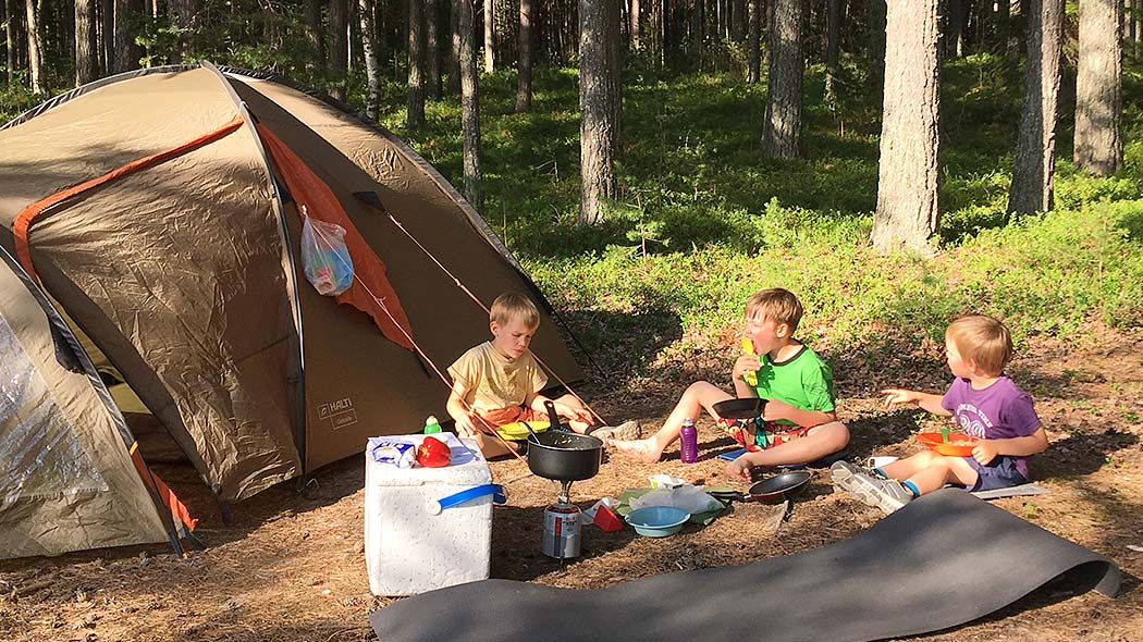Three children eating lunch next to their tent.