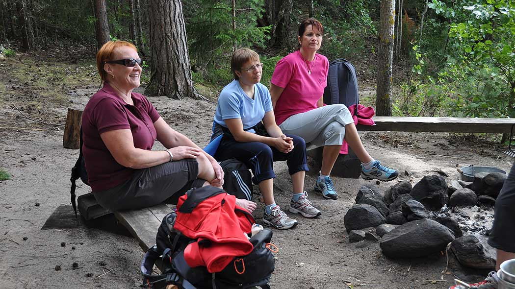 Three hikers by a campfire site.