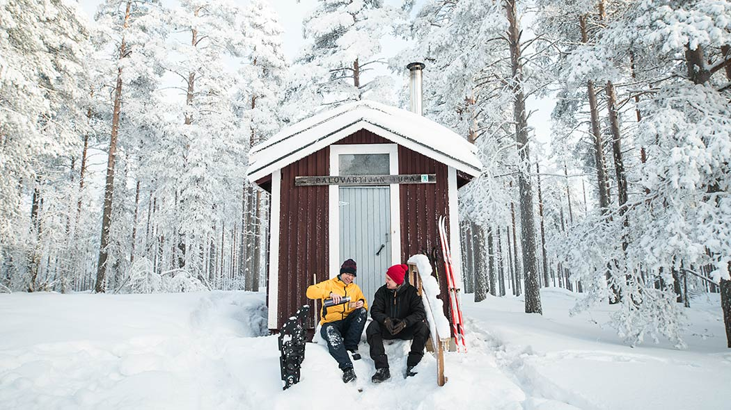Two skiers are having a break on the stairs of the Palovartija wilderness hut in the middle of a snowy forest.
