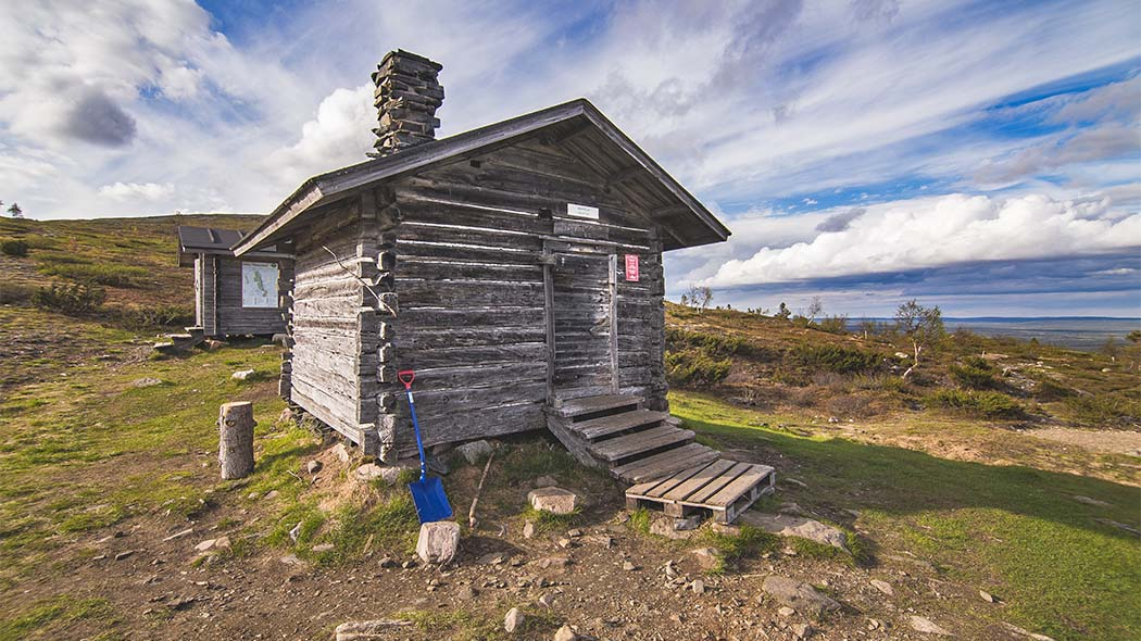 An open wilderness hut on the slope of a fell.