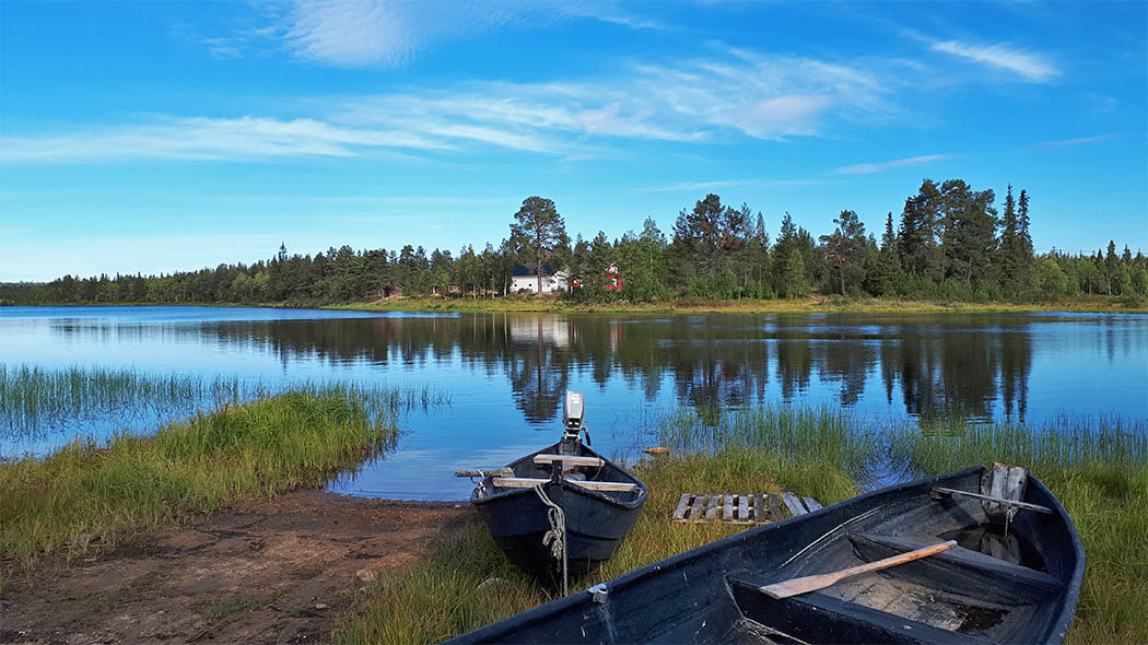 Two rowboats on the shore of River Ounasjoki. On the opposing shore are houses and a forest.